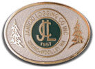Logging belt buckle with color fill and fir trees on either side of oval buckle