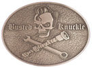 Skull and tools on this oval belt buckle with antique stippled background