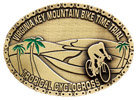 Mountain biking belt buckle with palm trees and desert in background